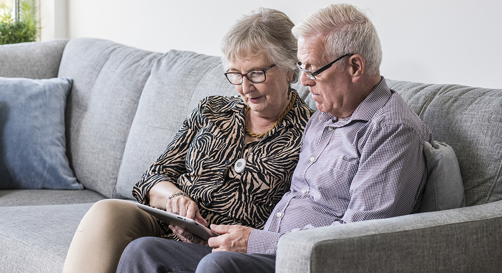 An elderly couple using their ipad device