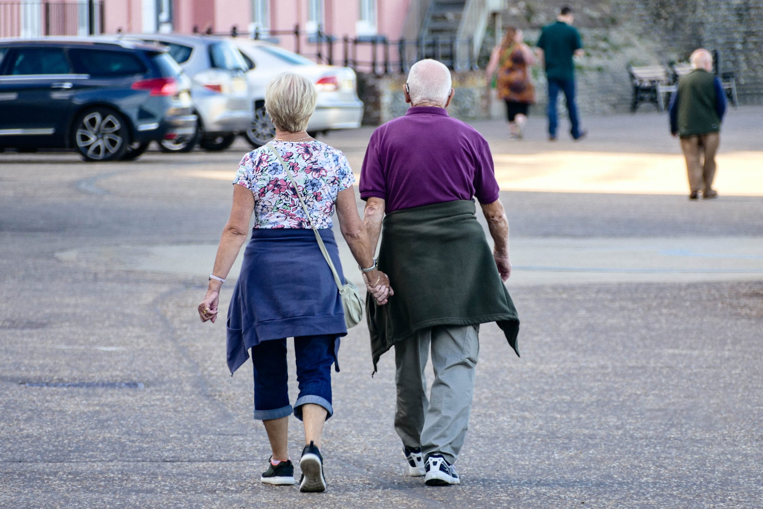 Older couple walking holding hands