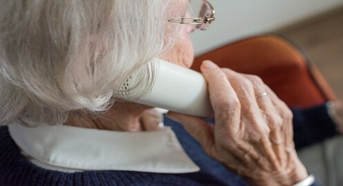 An elderly lady speaking on their telephone