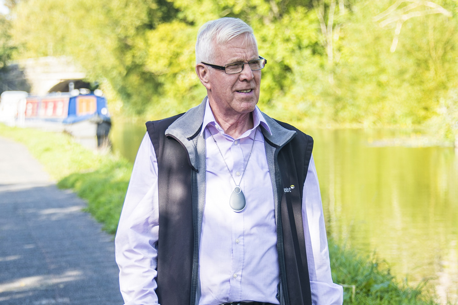 Older man walking along a canal