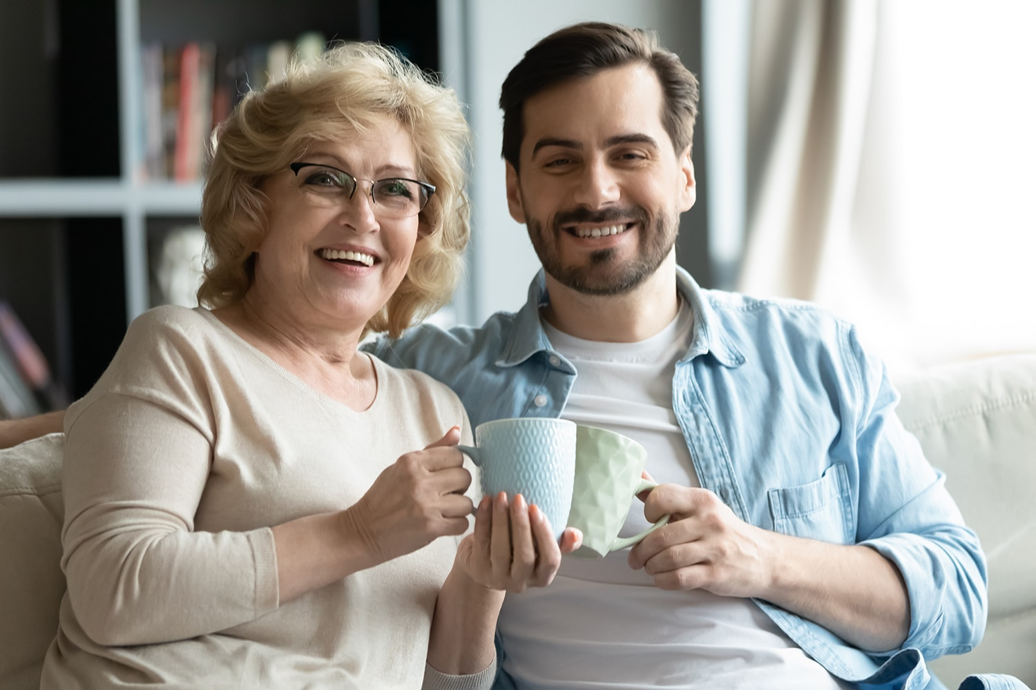 Happy mature mom and adult son relax drinking tea