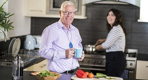elderly man in his kitchen with a loved one