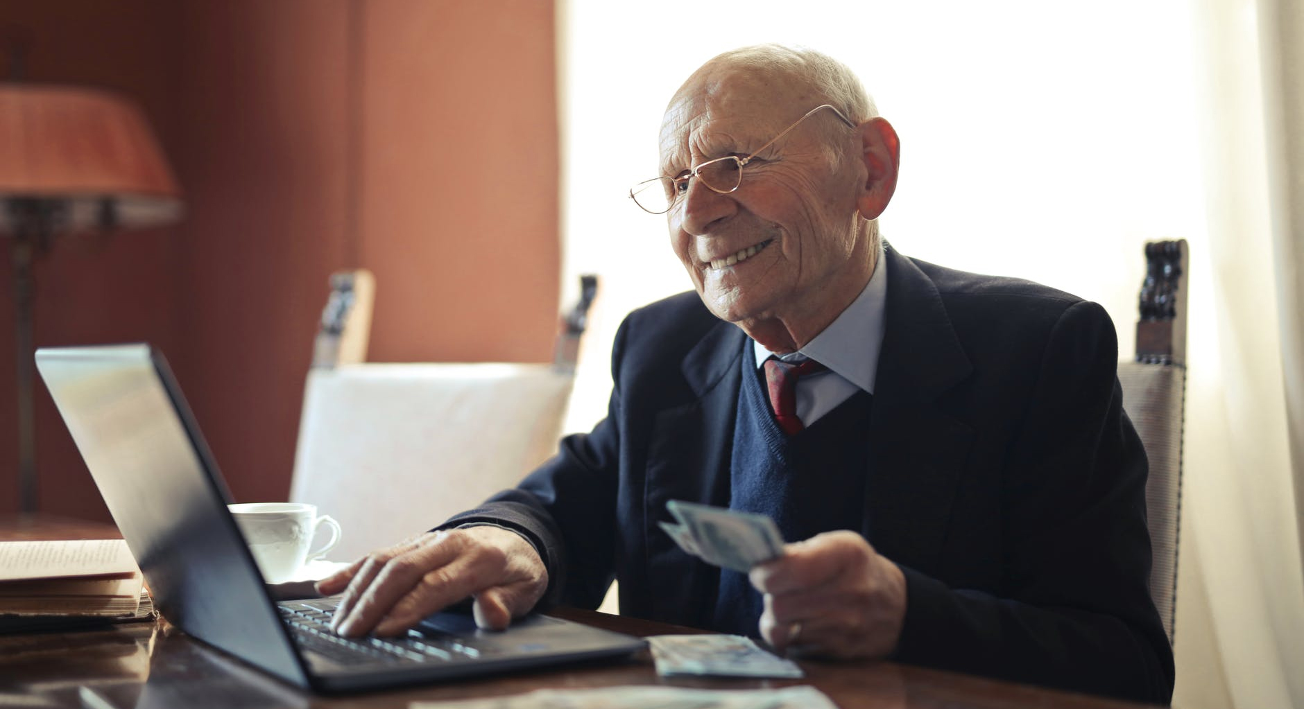 An elderly many at a laptop holding cash in his hand