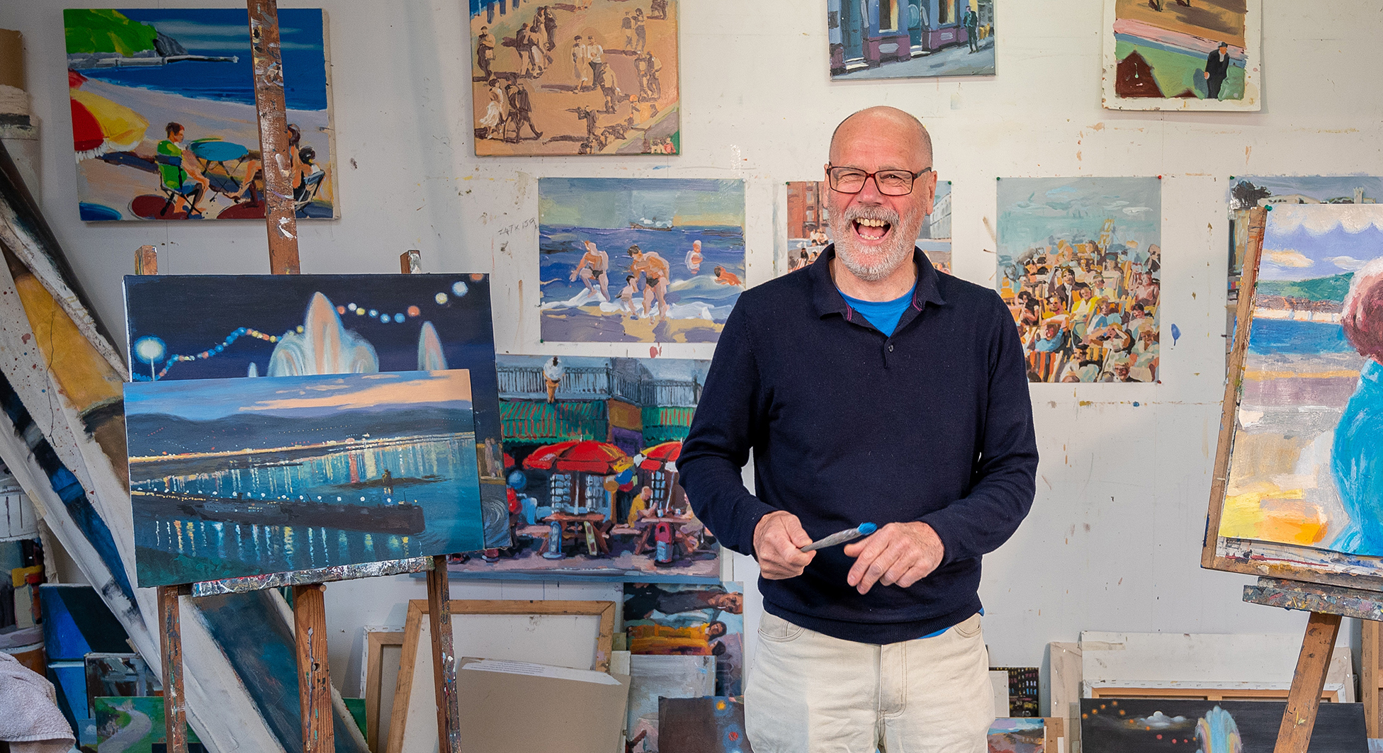 Laughing older man standing in front of paintings