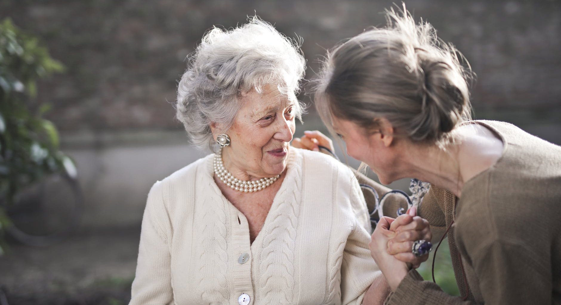 Smiling older woman holding hands with a younger woman