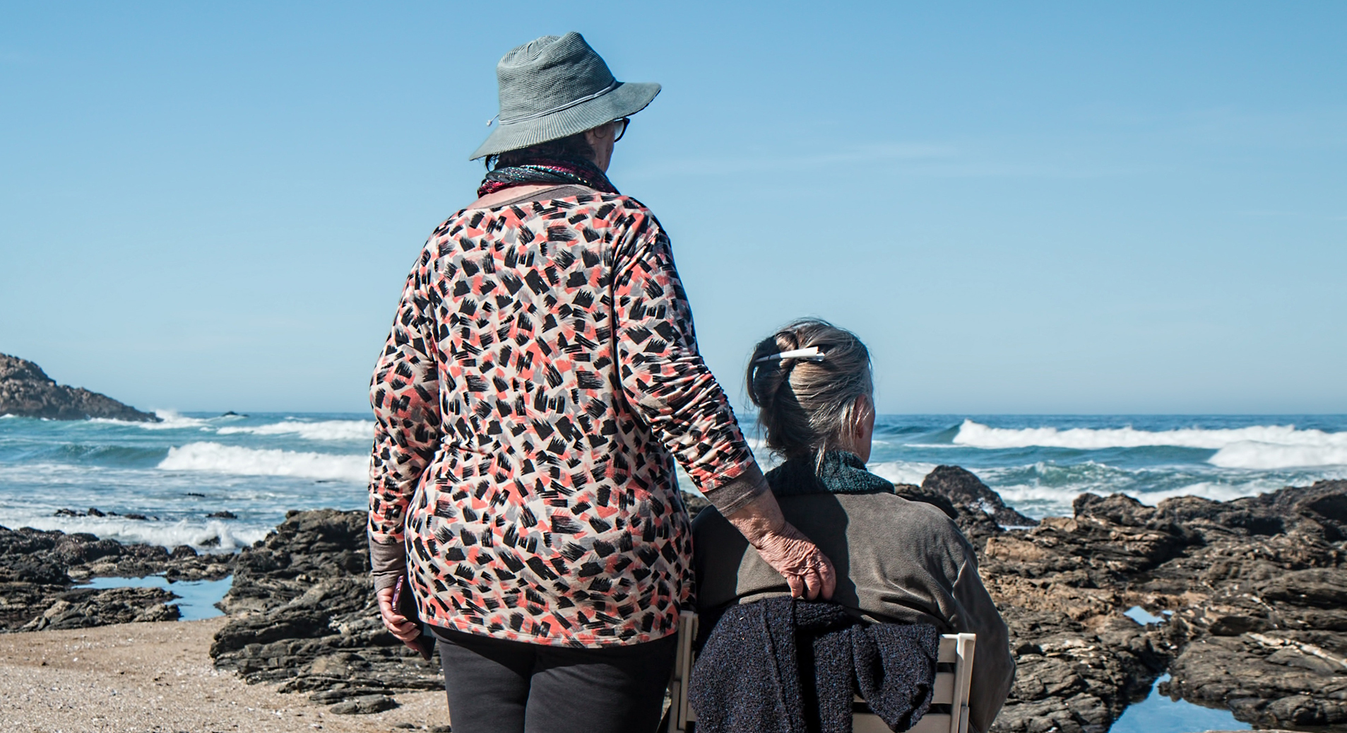 Two older women on a beach looking out to sea